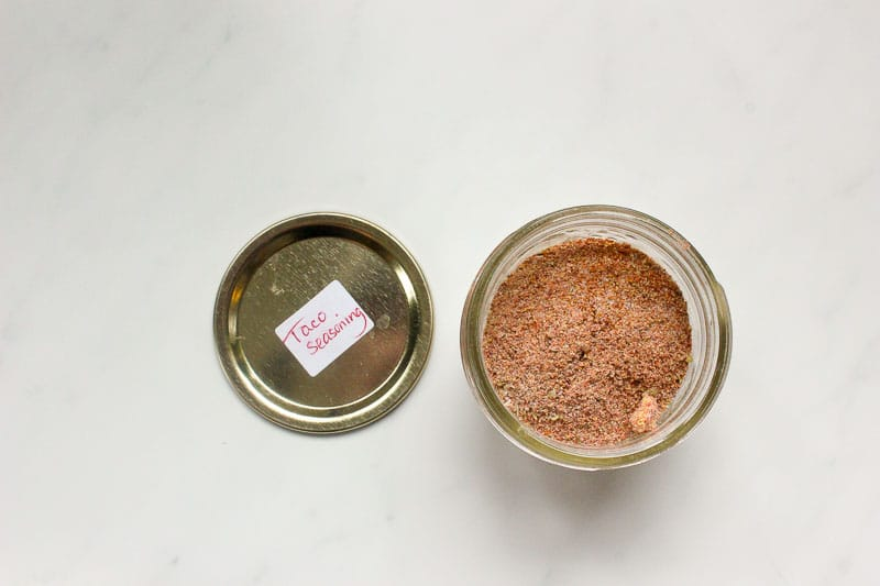 "Small mason jar with spice mixture in it and lid with ""Taco Seasoning"" label sitting on a marble surface."