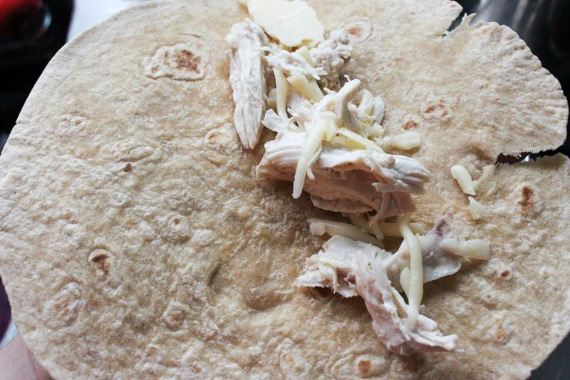 Putting Shredded Chicken and Shredded Mozzarella Cheese in Tortilla.