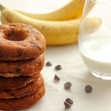 Stack of chocolate chip donuts with bananas and glass of milk.