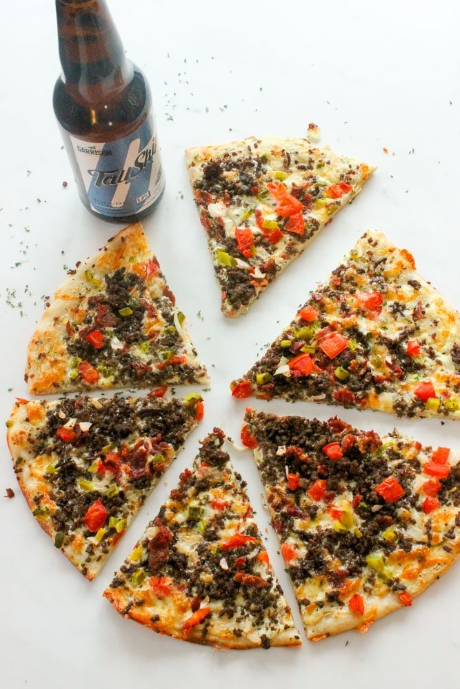 Sliced Bacon Cheeseburger Pizza and Bottle of Beer on White Background.