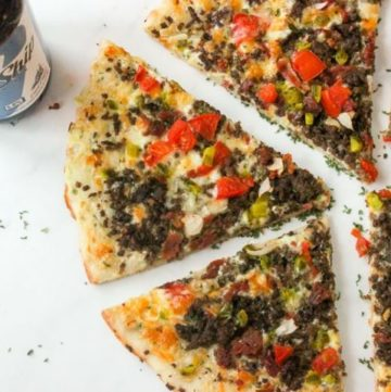 Pizza slices topped with beef and vegetables on white background.