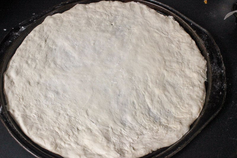 Pizza Dough Spread on Round Metal Pizza Pan.