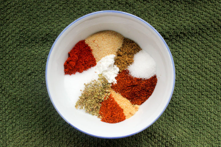 Small bowl full of colourful herbs and spices on a green cloth.