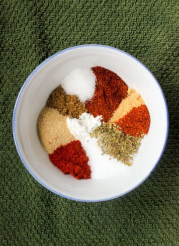Small white bowl full of colourful herbs and spices.