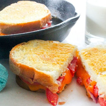 Sliced grilled cheese with tomato.