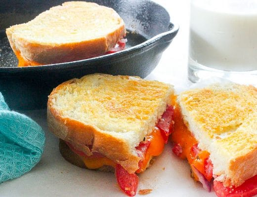 Grilled tomato and cheese sandwich cut open, with melty cheese. A glass of milk, a blue cloth, and a cast iron frying pan holding another sandwich in the background.