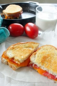 Grilled sandwich with cheese and tomato cut open to reveal melted cheese, with two tomatoes, a glass of milk and a cast iron frying pan holding another grilled cheese sandwich in the background.