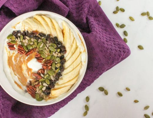White bowl with yogurt, peanut butter, sliced banana, raisins, sunflower seeds and pumpkin seeds, with a purple cloth, with pumpkin seeds sprinkled around.