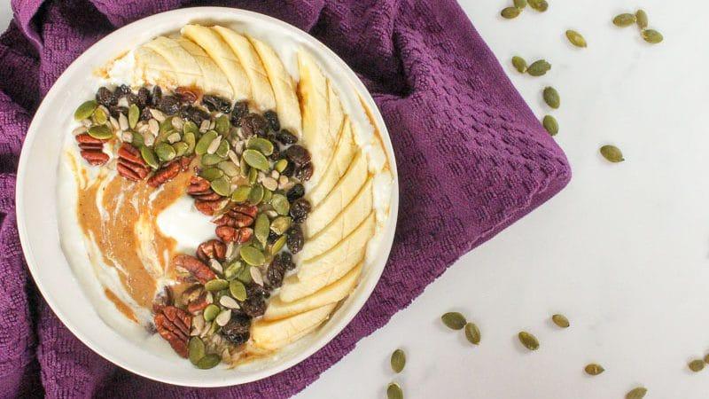 White bowl with yogurt, peanut butter, sliced banana, raisins, sunflower seeds and pumpkin seeds, with a purple cloth, with pumpkin seeds sprinkled around.