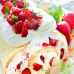 Cake topped with whipping cream and strawberries.