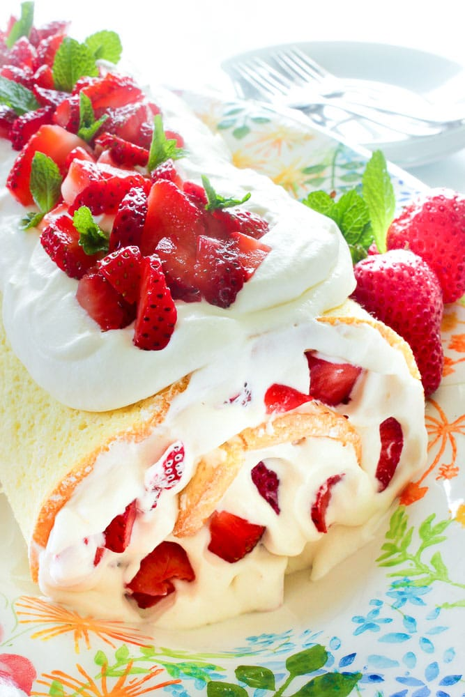 White cake roll, stuffed with whipped cream and sliced strawberries, with whipped cream, and sliced strawberries on top, garnished with mint leaves, on a colourful platter. Plates and forks in the background.
