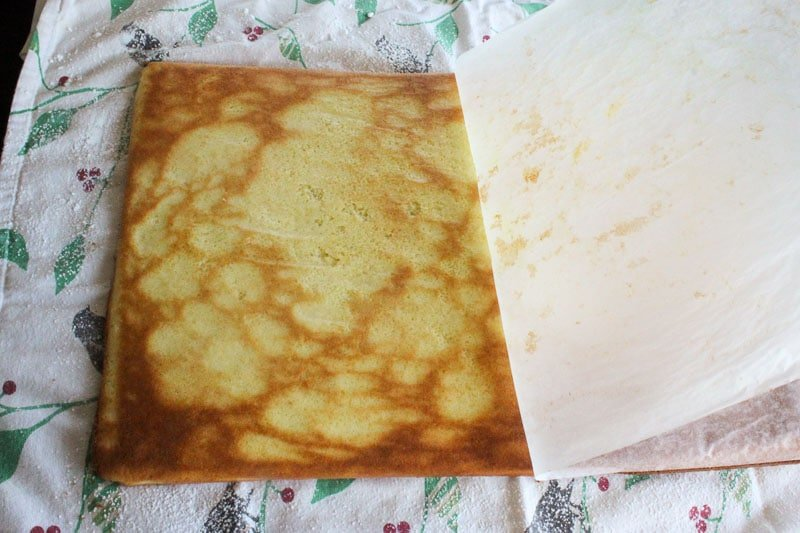 Sheet pan cake on a tea towel, with parchment paper being peeled off