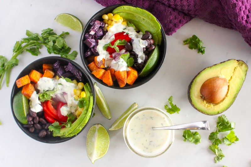 Colourful Vegetables Topped with Cilantro and Lime Sauce in Black Bowls.