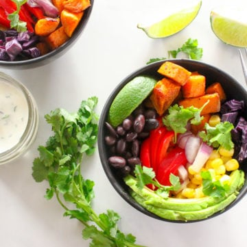 Two black bowls, filled with cubes of sweet potato, sliced red pepper, black beans, diced red onion, sliced avocado, kernels of corn and pieces of red cabbage, set on a table with a white sauce in a jar, some lime wedges and a bunch of loose cilantro
