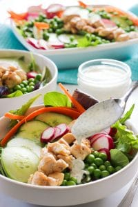 Salad bowls with lettuce, cucumber, radish, carrots, peas and a creamy herb dressing.