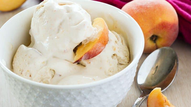 Peach ice cream in a white bowl