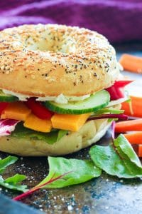 Everything bagel sandwich with vegetables and cheese.
