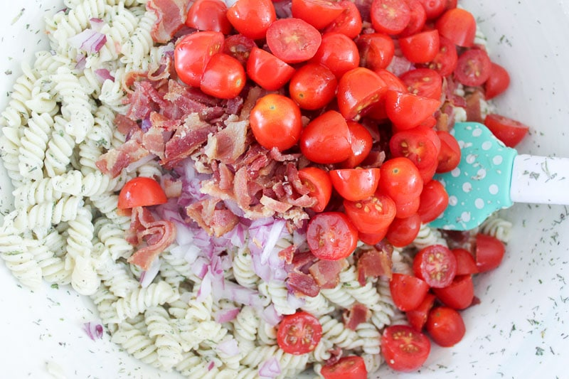 Rotini pasta, creamy ranch sauce, bacon, tomatoes and red onions in mixing bowl