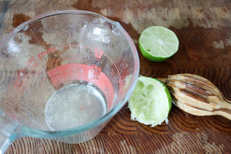 Lime juice in Glass Measuring Cup with limes and reamer on wooden board.