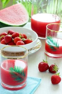 Strawberry Watermelon Juice in Glasses next to white bowl filled with strawberries.
