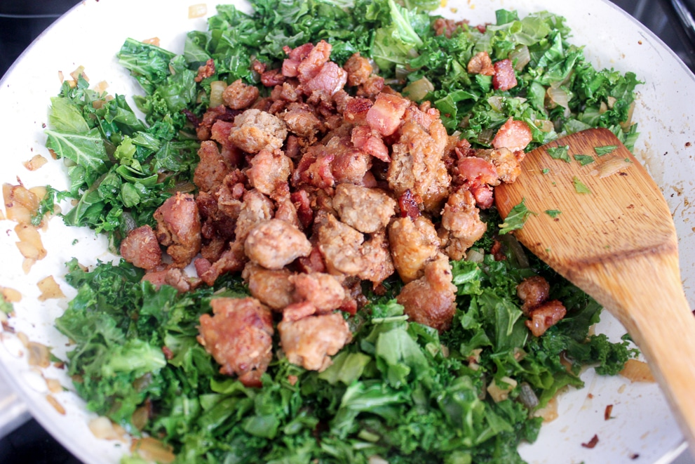 Chopped kale in a skillet with browned sausage and bacon on top of it