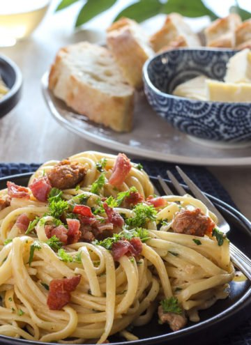 Pasta with sausage and bacon on black plate.