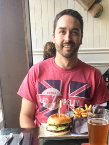 A man smiling sitting in front of a burger and fries.
