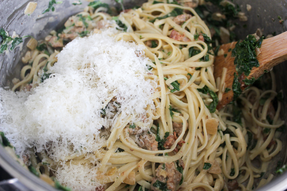 Linguine pasta noodles with sausage, bacon, kale, cream and Parmesan cheese mixed in