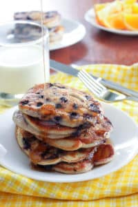 Stack of blueberry pancakes on plate, with stream of syrup pouring on them and glass of milk