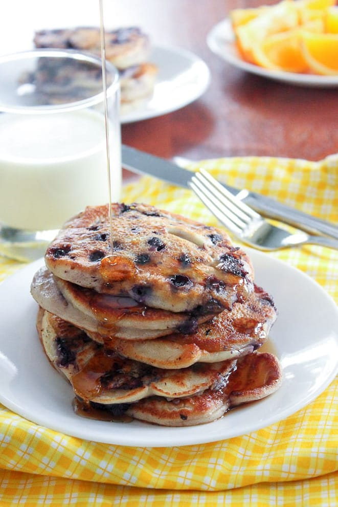 Stack of blueberry banana pancakes and glass of milk