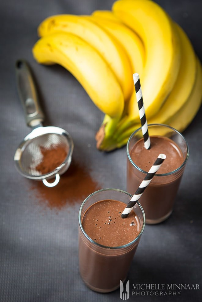 Glasses of chocolate banana protein shake with bunch of bananas