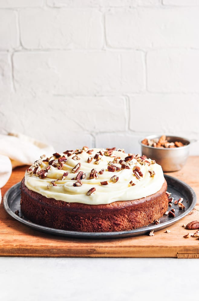 Banana cake with nuts on top of cream cheese frosting