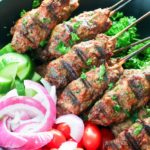 Large bowl of grilled hamburger kebabs and vegetables