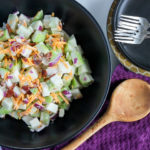 Chayote salad in black serving bowl, with side plates and forks