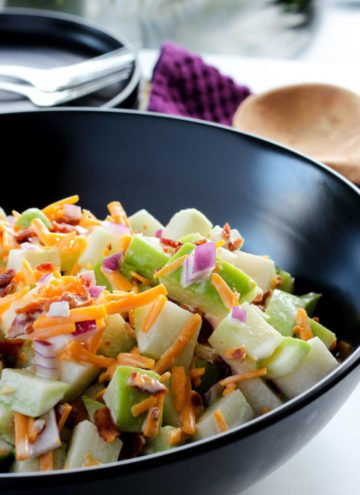 Large black bowl full of creamy chayote squash salad with bacon, cheddar cheese and onions