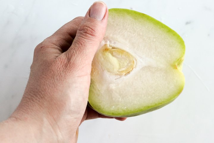 Hand holding half a chayote squash