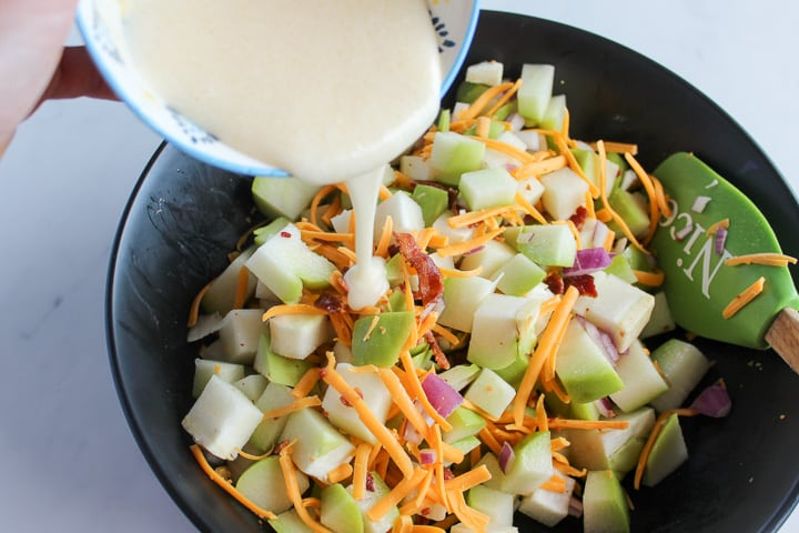 Pouring dressing into bowl of chayote squash salad ingredients