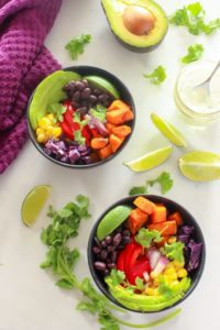 Bowl of mexican roasted sweet potatoes, black beans, red pepper, corn, avocado, limes, cilantro