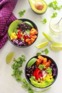 Bowl of mexican roasted sweet potatoes, black beans, red pepper, corn, avocado, limes and cilantro.