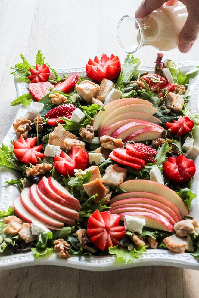 Platter of Strawberry Chicken Salad with dressing being poured on