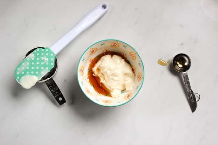 Bowl with mayonnaise and maple syrup in it, with spatula and measuring tools