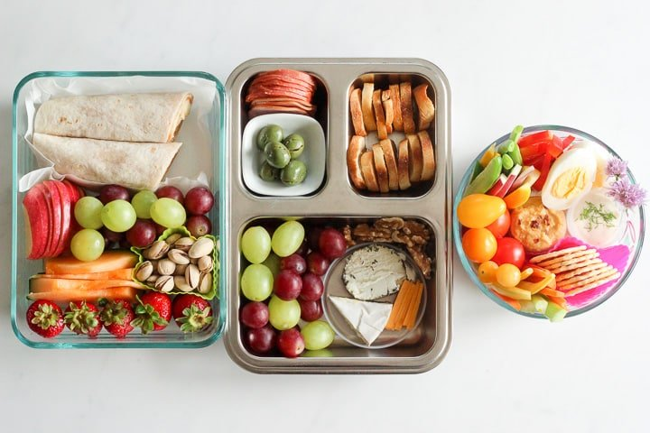 Three containers of mix and match bistro box style lunches - with fruit, wraps, meat, cheese, crackers, nuts and hardboiled eggs