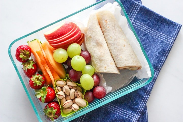 Dish of apples, strawberries, grapes, pistachios and a banana peanut butter wrap
