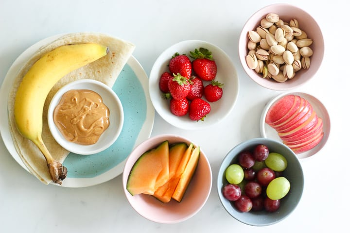 Plate with banana, tortilla and peanut butter, dishes holding strawberries, pistachios, cantaloupe, grapes and apple