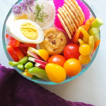 Dish with hardboiled egg, rice crackers, cherry tomatoes, carrot sticks, fresh green and yellow beans, hummus and ranch dip