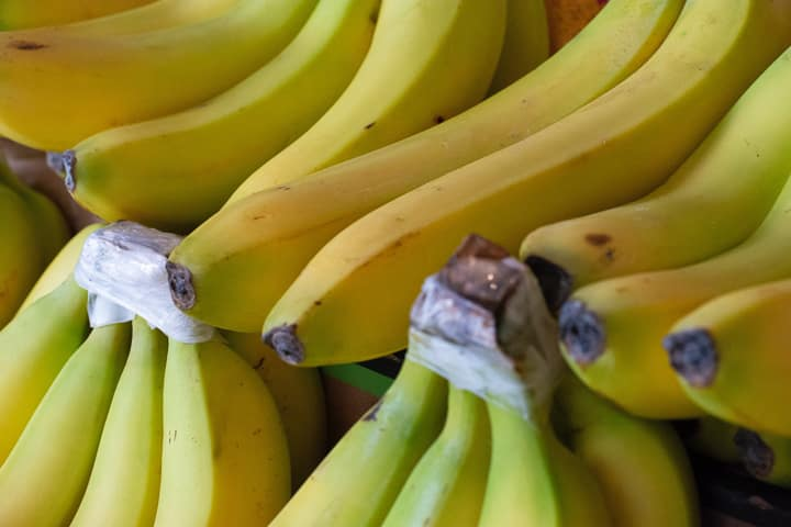 Many bunches of bananas with tops wrapped in plastic to last longer