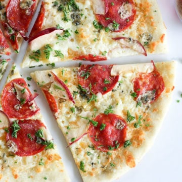Thin crust pizza with Italian salami, mozzarella cheese, apple, blue cheese and parsley