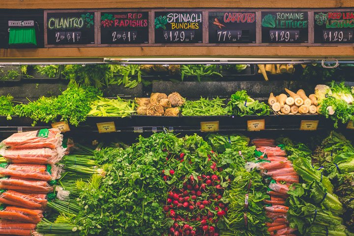 Grocery store shelves with fresh vegetables - carrots, herbs, radishes, lettuce