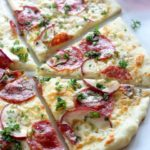 Thin crust pizza with salami, blue cheese, apple and parsley.