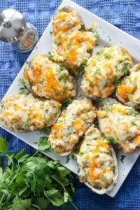 Baked potatoes covered in cheese and parsley on serving plate